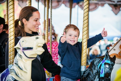 Boy with Two Thumbs Up with Mother on Carousel