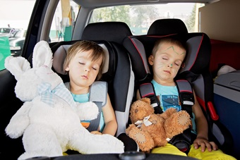 Two boys in car seats, travelling