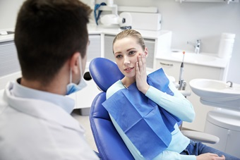 male dentist with woman patient at clinic