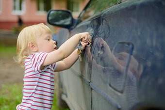 little boy with car keys opening car door