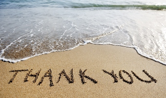 Thank you words drawn in sand