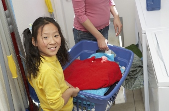 Girl helping mother to wash clothes
