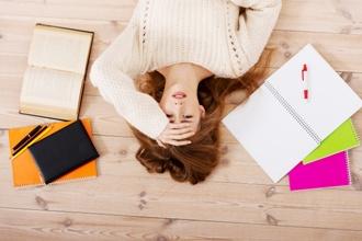 girl lying on floor engaged in procrastination