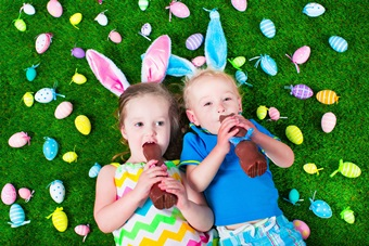 Kids eating chocolate rabbit on Easter egg hunt