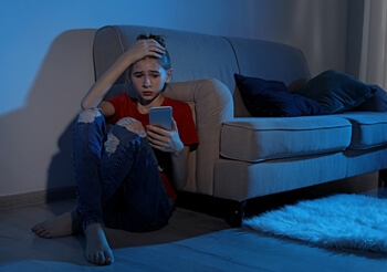 Upset teenage girl with smartphone in dark room